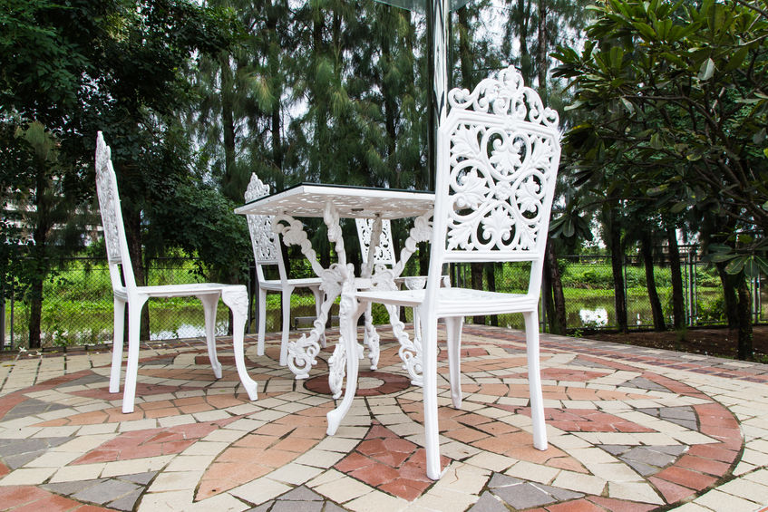 47190858 - white iron chair in garden with trees.
